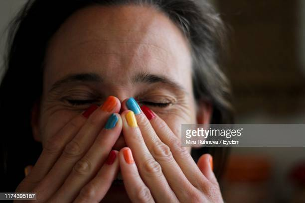 close-up of smiling woman with hands covering mouth - nail art stock pictures, royalty-free photos & images