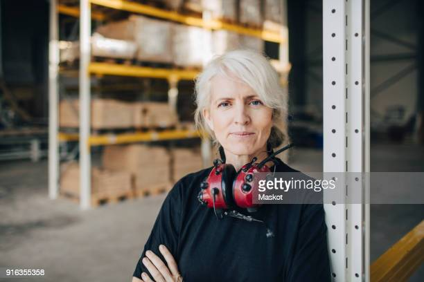 close-up of smiling worker standing with arms crossed by rack of industry - berufliche beschäftigung stock-fotos und bilder