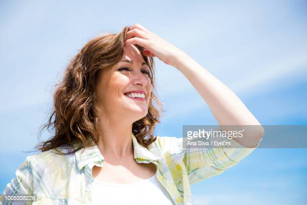 Close-Up Of Smiling Young Woman Against Sky