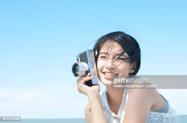 Close-Up Of Smiling Young Woman Holding Camera Against Sky