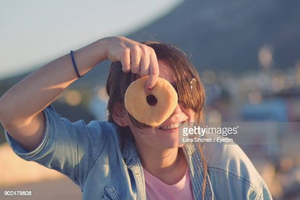 Close-Up Of Smiling Young Woman Holding Donut