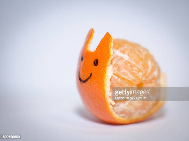 Close-Up Of Snail Made Of Orange On White Background