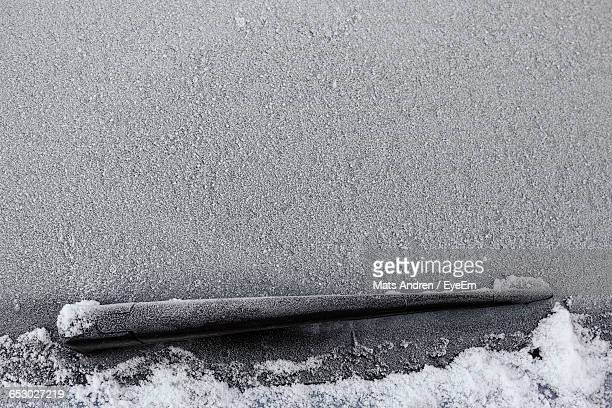 close-up of snow covered windshield - windshield wiper stock photos and pictures