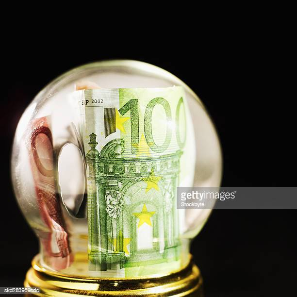 Close-up of snow globe containing euro bank notes