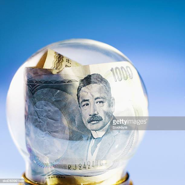 Close-up of snow globe containing Japanese yen bank notes