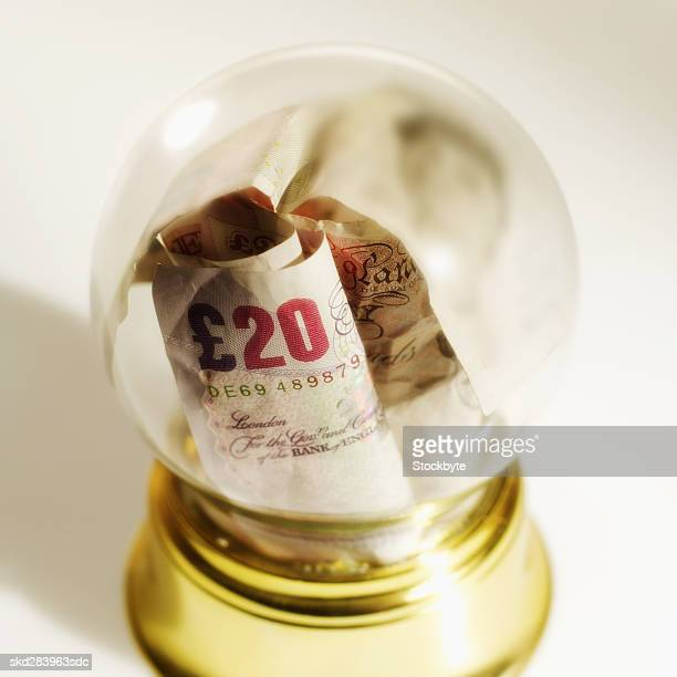 Close-up of snow globe containing U.K.. pound notes