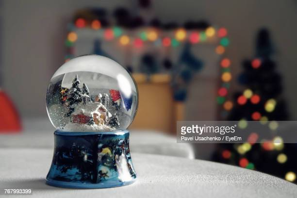 Close-Up Of Snow Globe On Table With Christmas Tree In Background