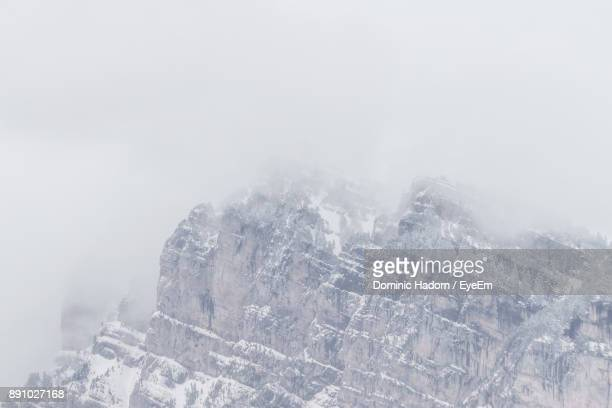 Close-Up Of Snow On Mountain Against Sky During Foggy Weather