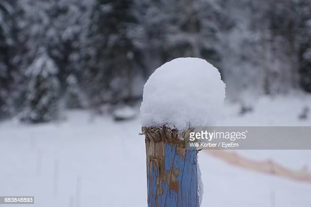 Close-Up Of Snow On Wooden Post Over Field