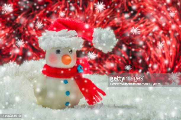 close-up of snowman against illuminated light in snow - snowflake vector stock photos and pictures