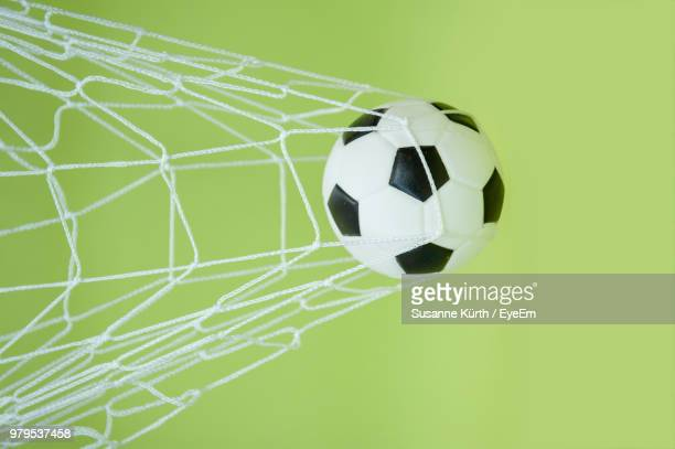Close-Up Of Soccer Ball In Net Against Green Background