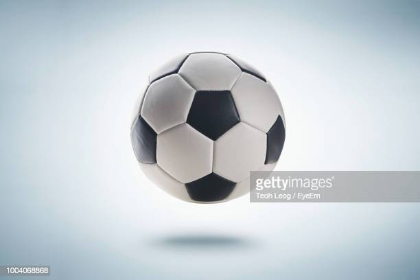 close-up of soccer ball levitating against white background - palla sportiva foto e immagini stock