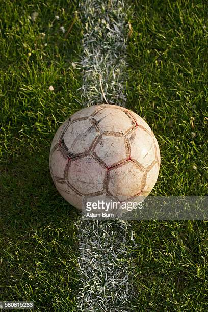 Close-up of soccer ball on white line in stadium