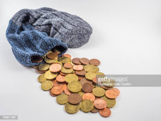 Close-Up Of Sock With Coins On White Background