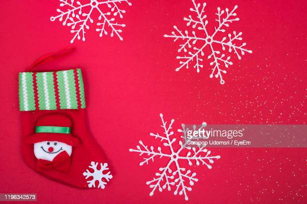 close-up of sock with snowflakes over red background - snowflake vector stock photos and pictures