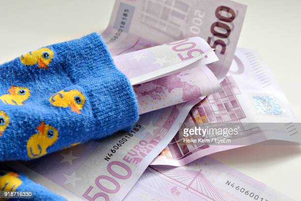 Close-Up Of Socks And Paper Currency On Table