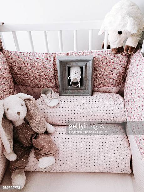 Close-Up Of Soft Toys And Shoes In Crib