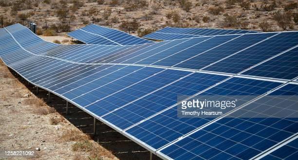 close-up of solar panels following the contour of sloping ground - timothy hearsum imagens e fotografias de stock