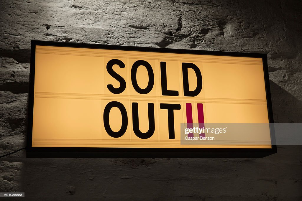 Close-up of Sold Out signboard against gray wall : ストックフォト