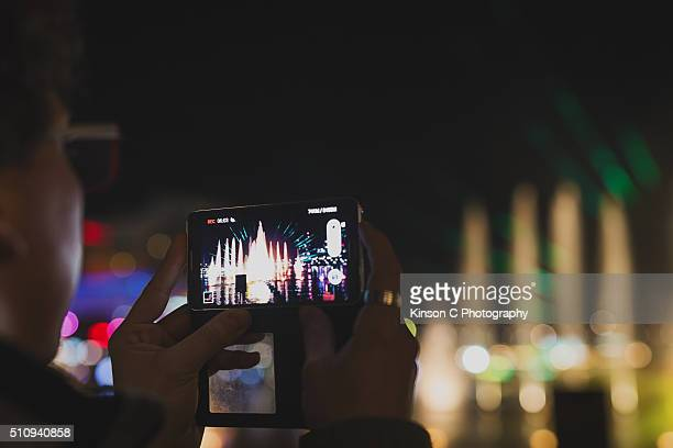 Closeup Of Someone Recording a Light show With His Smartphone