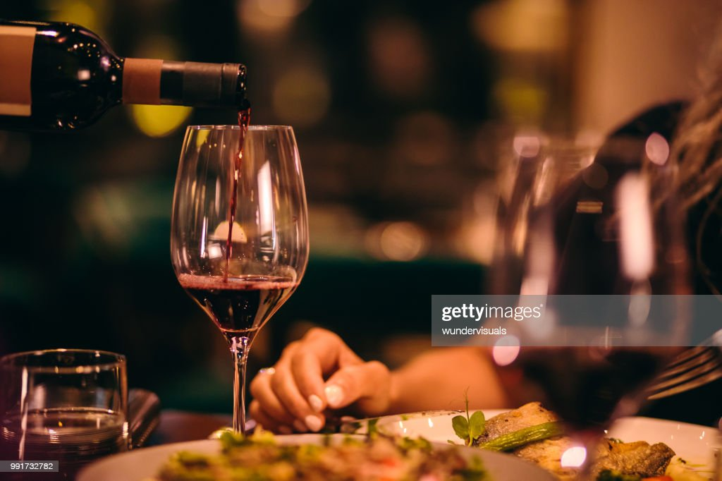 Close-up of sommelier serving red wine at fine dining restaurant : Stock Photo