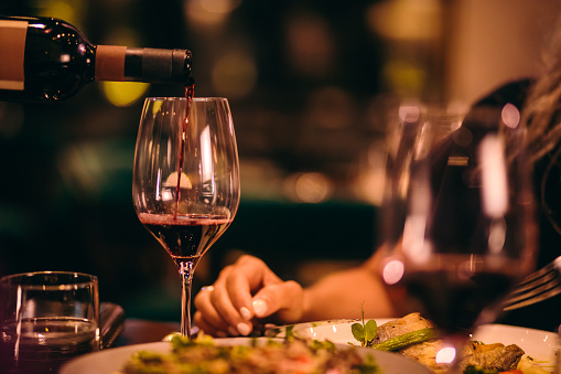 Close-up of sommelier serving red wine at fine dining restaurant 991732782
