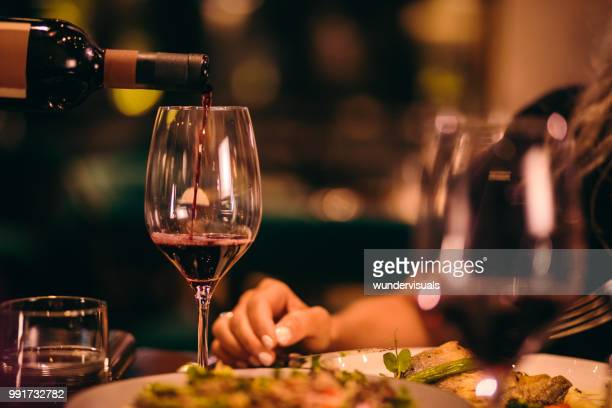 close-up of sommelier serving red wine at fine dining restaurant - wine glass stock pictures, royalty-free photos & images