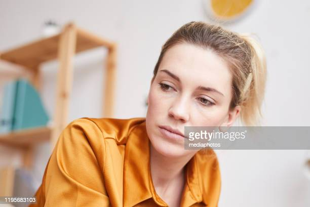 オレンジ色のブラウスを着た悲しい若い女性のクローズアップは、自分自身の落ち込んだ考えに焦点を当てながら下を見下ろしている - オレンジ色のシャツ ストックフォトと画像