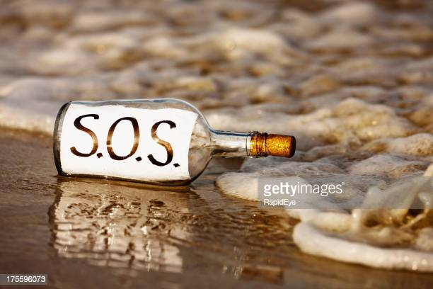 Close-up of SOS message in bottle at shoreline