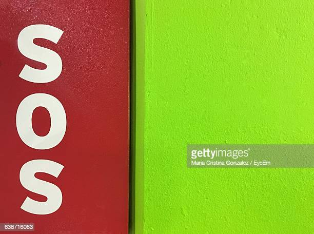 close-up of sos sign on wall - sos einzelwort stock-fotos und bilder