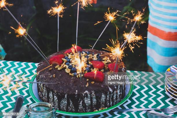 Close-Up Of Sparklers On Cake At Table