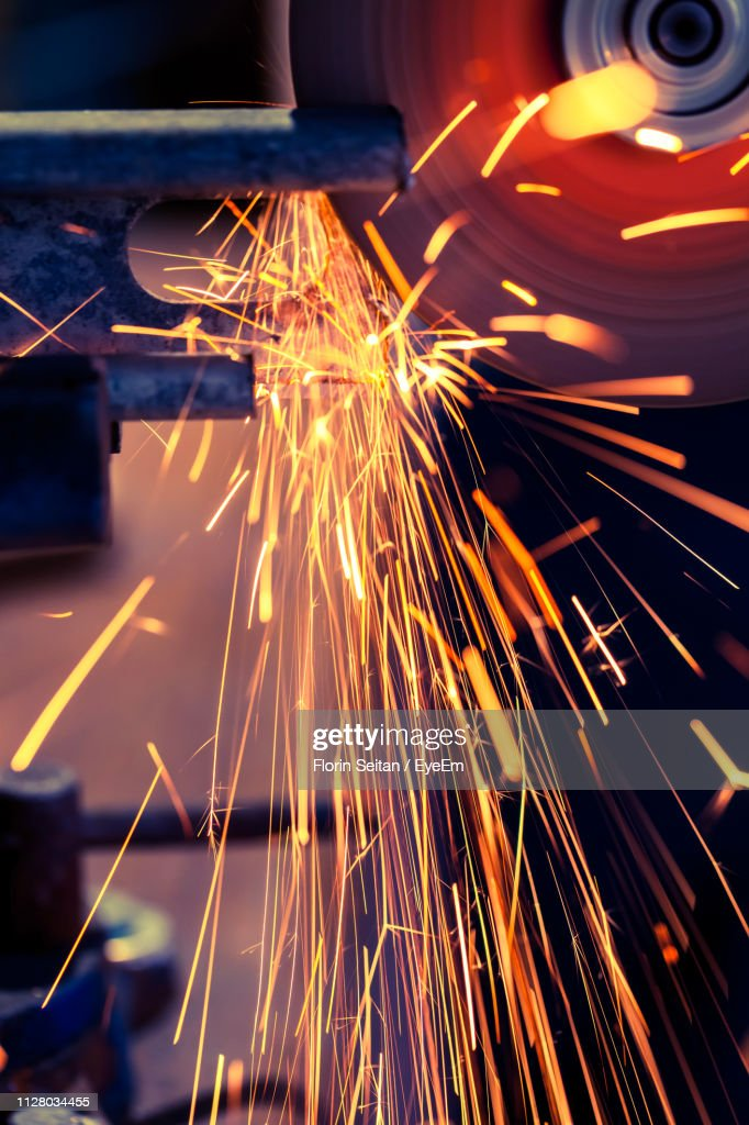 Close-Up Of Sparks Emitting From Saw : Stock Photo