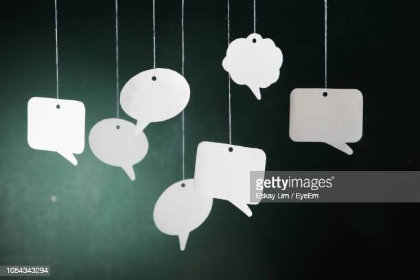 close-up of speech bubbles hanging against wall - speech bubble stock pictures, royalty-free photos & images