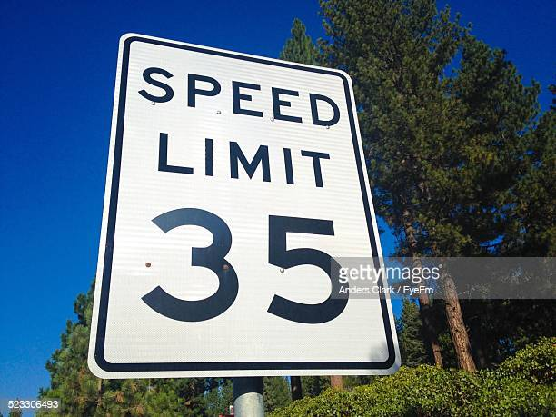 close-up of speed limit 35 sign against clear blue sky - speed limit sign stock photos and pictures