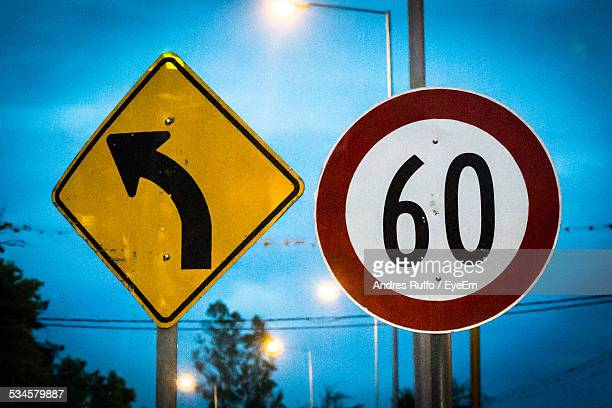 close-up of speed limit and arrow sign against sky - number 60 stock photos and pictures