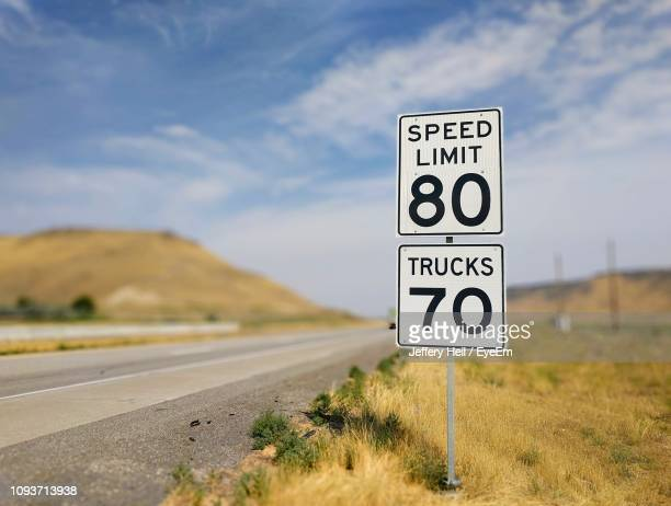 close-up of speed limit sign against sky - speed limit sign stock photos and pictures