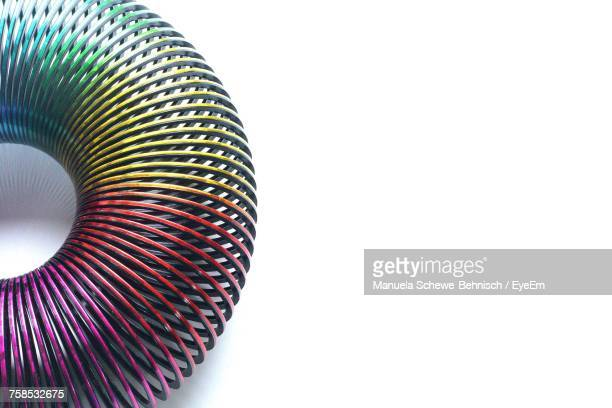 close-up of spiral metal against white background - metal coil toy stock photos and pictures