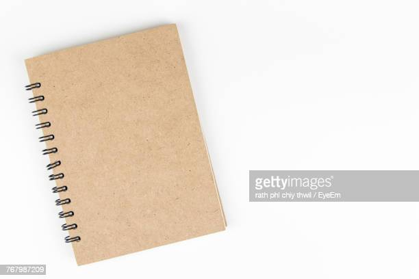 Close-Up Of Spiral Notebook Against White Background