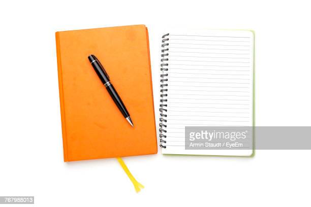 Close-Up Of Spiral Notebook And Pen Over White Background