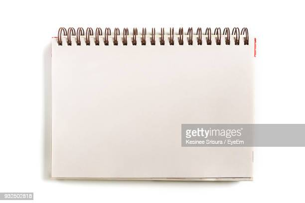 Close-Up Of Spiral Notebook Over White Background