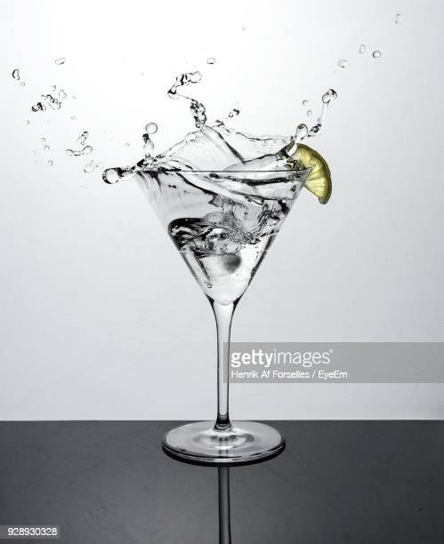 Close-Up Of Splashing Drink On Table Against White Background