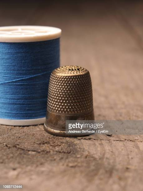 close-up of spool on table - thimble stock photos and pictures