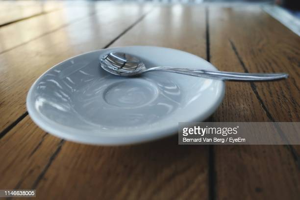 close-up of spoon on saucer at table - saucer stock pictures, royalty-free photos & images