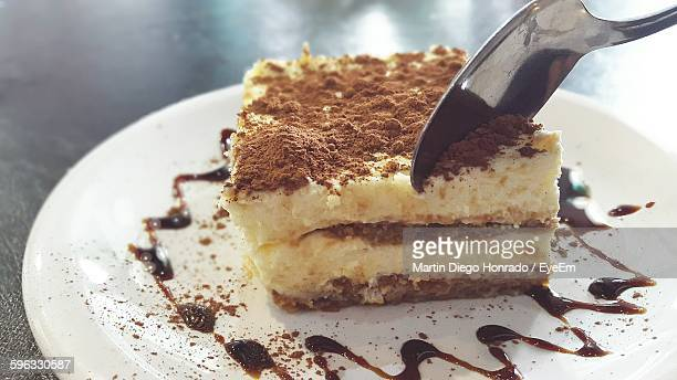 Close-Up Of Spoon On Tiramisu Served In Plate