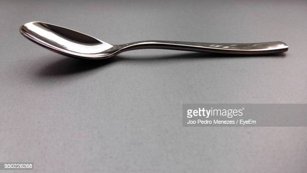 close-up of spoon over gray background - spoon stock pictures, royalty-free photos & images