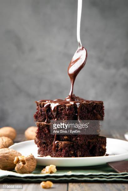 close-up of spoon pouring melting chocolate on sponge cake over table - dessert photos et images de collection