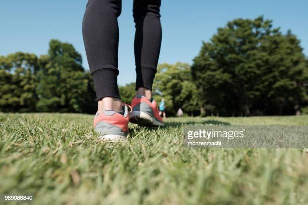 草の上を歩くスポーツの靴のクローズ アップ - 人の足 ストックフォトと画像