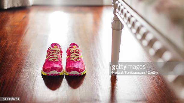 Close-Up Of Sports Shoes On Wooden Floor