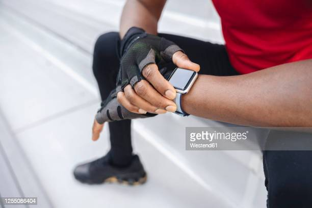 close-up of sportsman wearing smartwatch and gloves - smart watch stock pictures, royalty-free photos & images
