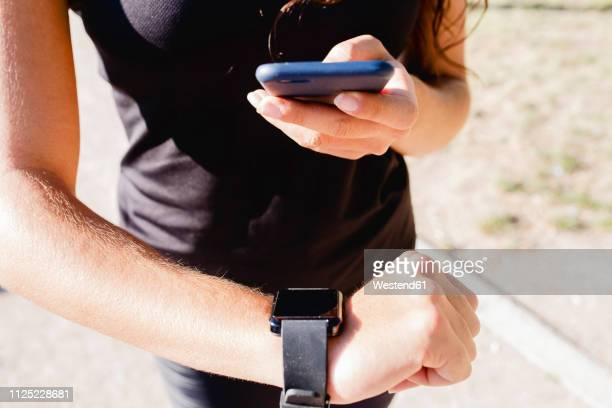 close-up of sporty young woman using cell phone and smartwatch - checking sports stock pictures, royalty-free photos & images